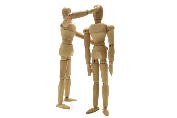 Wooden figures correcting each other postures.